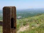 Denver skyline from behind a wooden fence post on top of Green Mountain